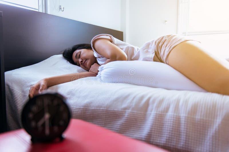 Fine su della donna che dorme sul letto nella camera da letto con il fondo della sfuocatura della sveglia immagine stock libera da diritti