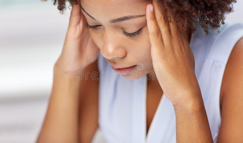 Fine su della giovane donna africana che tocca la sua testa fotografia stock libera da diritti