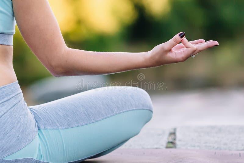 Fine su della mano della giovane donna che si siede nella posa del loto immagini stock libere da diritti
