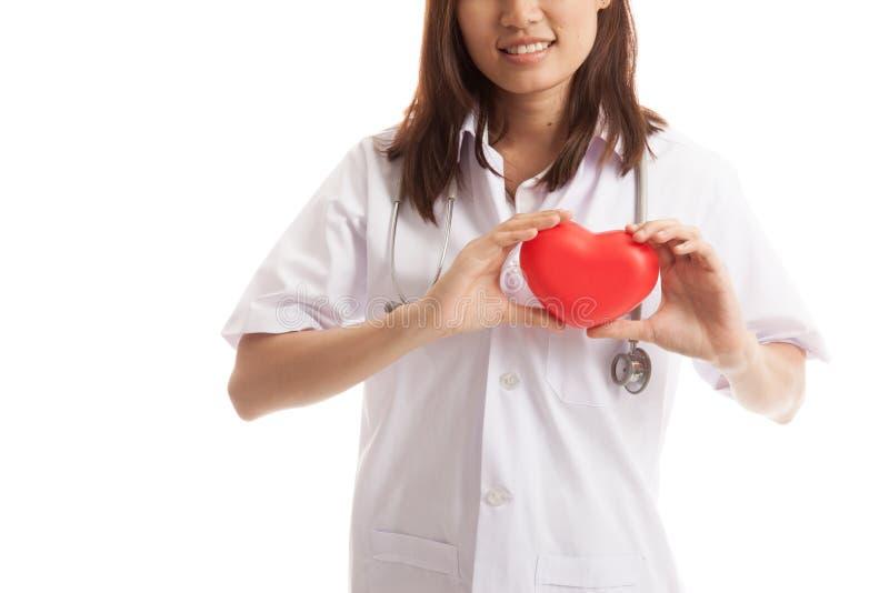 Fine su della tenuta femminile asiatica di medico un cuore rosso e fotografia stock libera da diritti