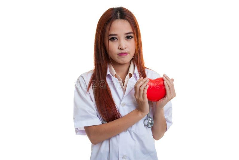 Fine su della tenuta femminile asiatica di medico un cuore rosso e fotografia stock