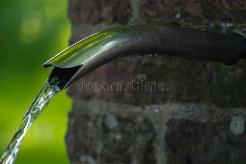 Fine su di acqua corrente da un rubinetto del metallo fotografie stock