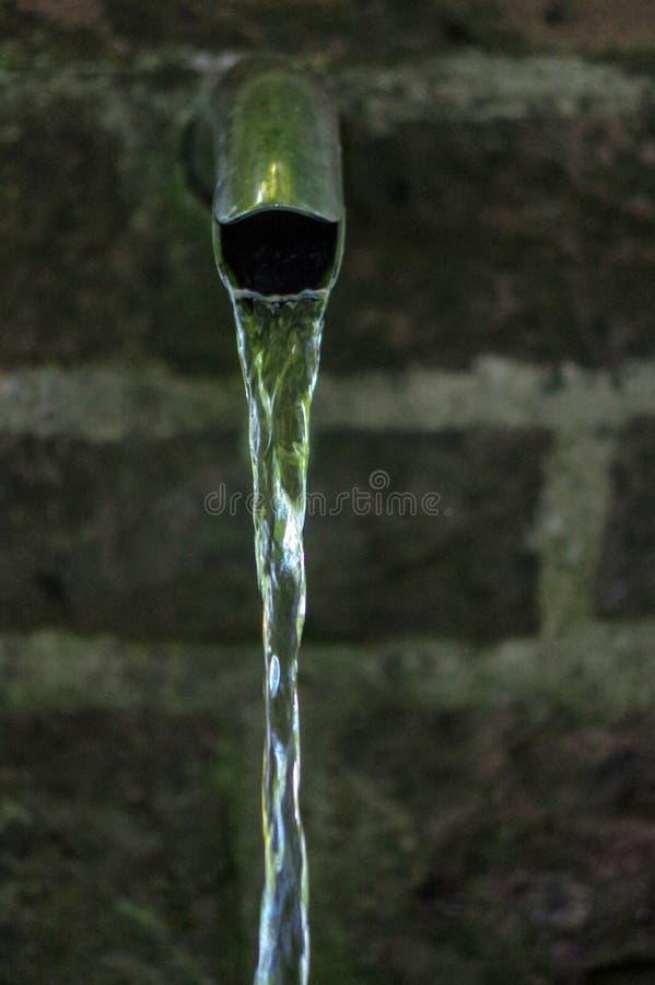 Fine su di acqua corrente da un rubinetto del metallo fotografia stock