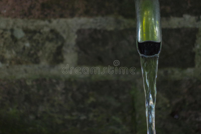 Fine su di acqua corrente da un rubinetto del metallo fotografie stock libere da diritti