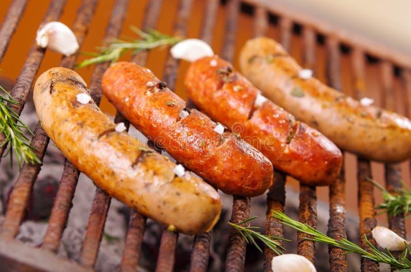 Fine su di quattro salsiccie grigliare sulla griglia del barbecue con alcune specie BBQ nel giardino Salsiccie bavaresi immagine stock libera da diritti