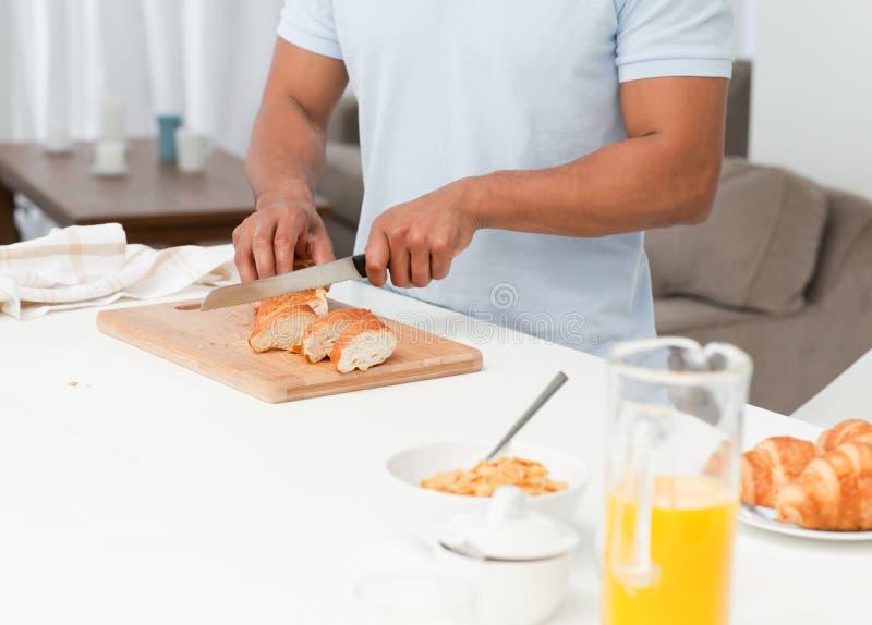 Fine in su di un pane di taglio dell'uomo durante la prima colazione immagine stock libera da diritti