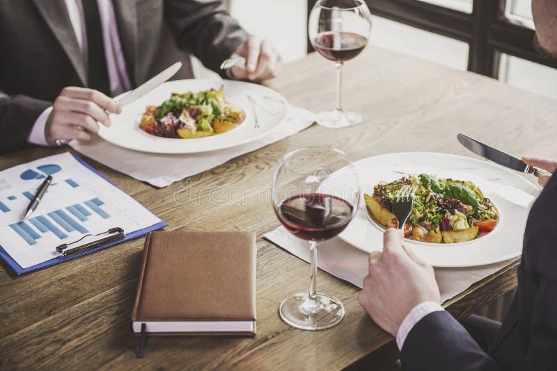 Fine in su Due uomini d'affari pranzano con vino fotografia stock libera da diritti