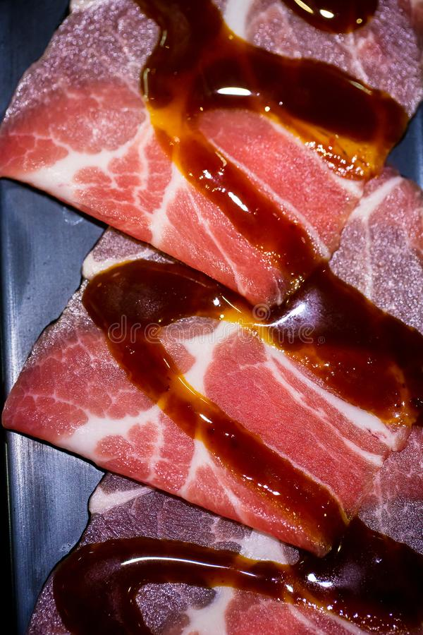 Fine in su Faccia scorrere la carne di maiale ed il manzo crudi di wagyu su una banda nera fotografia stock libera da diritti