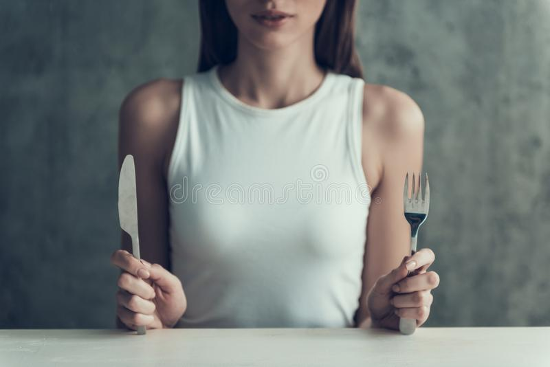 Fine in su Giovane donna che si siede con il coltello e la forcella fotografie stock