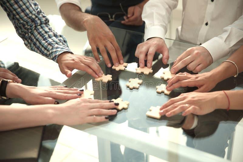 Fine in su gruppo di affari che collega i pezzi di puzzle fotografie stock
