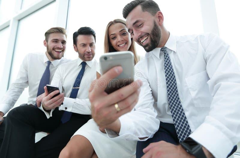 Fine in su gruppo sorridente di affari che discute SMS immagine stock