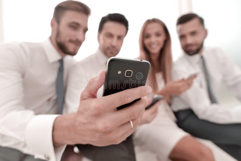 Fine in su gruppo sorridente di affari che discute SMS immagini stock
