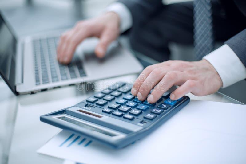 Fine in su l'uomo d'affari effettua i calcoli sul calcolatore fotografia stock