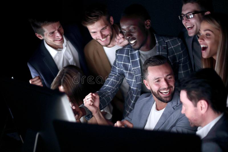 Fine in su La gente di affari allegra esamina lo schermo di computer fotografia stock libera da diritti
