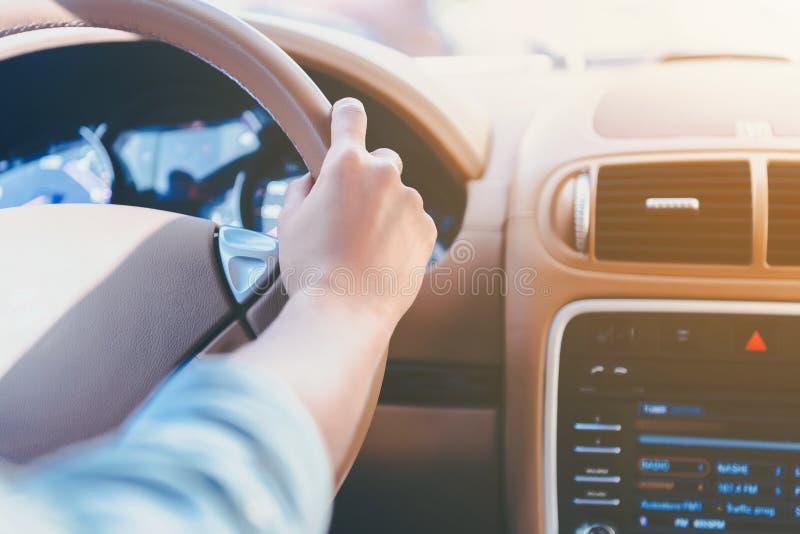 Fine in su La ragazza conduce l'automobile con la mano dietro la ruota immagini stock