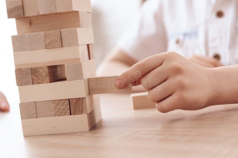 Fine in su Padre adulto con i piccoli giochi Jenga del figlio a casa immagini stock