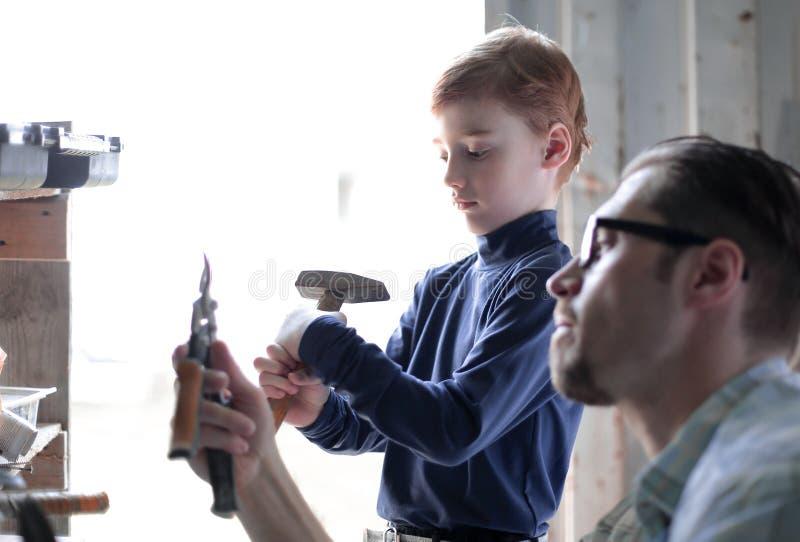 Fine in su padre e figlio nel garage domestico fotografie stock