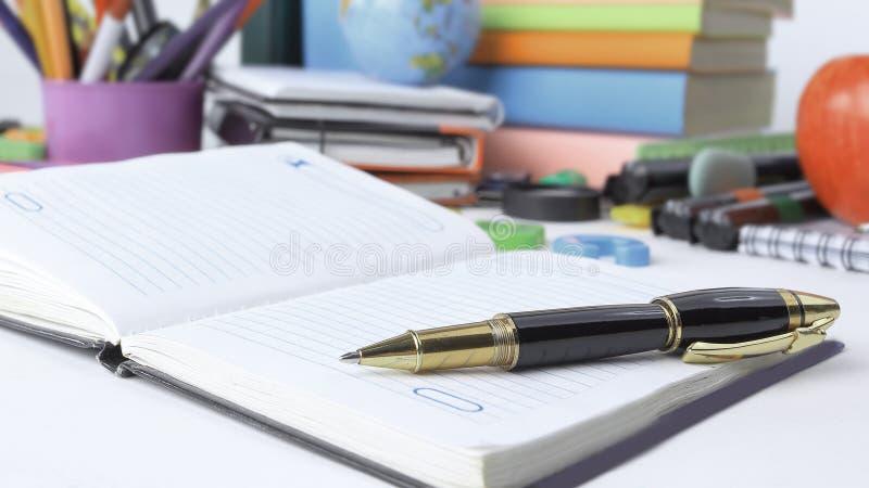 Fine in su rifornimenti del taccuino, della penna e di scuola isolati su fondo bianco Foto con lo spazio della copia immagini stock