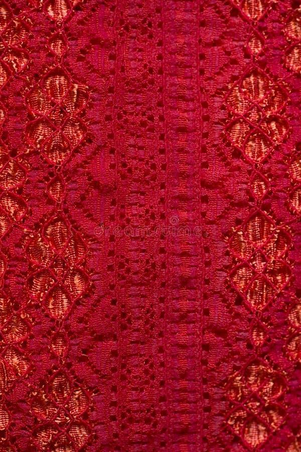 Fine su struttura rosso-arancio del pizzo del materiale del panno fotografia stock