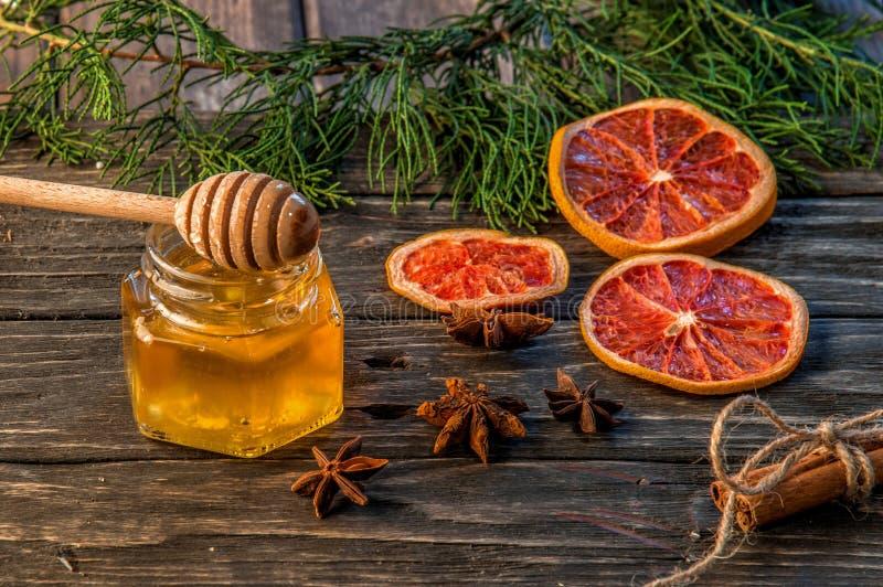 Fine in su Un barattolo di vetro di miele dorato, su là è un merlo acquaiolo del miele con le gocce spesse scorrenti Vicino sono  fotografia stock libera da diritti