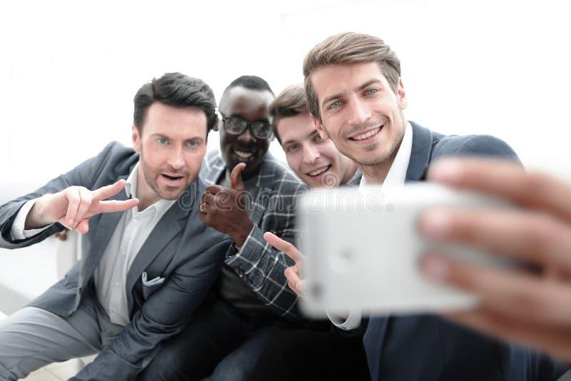 Fine in su un gruppo di giovani impiegati prende un selfie immagini stock libere da diritti