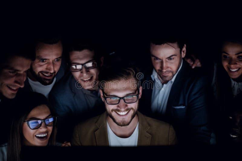 Fine in su un gruppo di impiegati che lavorano tardi nell'ufficio fotografia stock