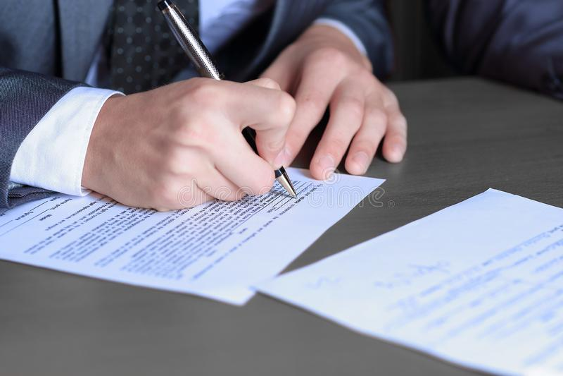 Fine in su uomo d'affari che compila la forma del contratto immagine stock