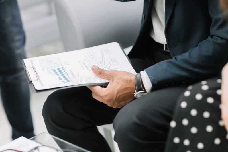 Fine in su uomo d'affari con i documenti finanziari che si siedono alla scrivania immagini stock