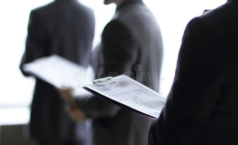 Fine in su uomo d'affari con una lavagna per appunti sui precedenti dei colleghi immagini stock