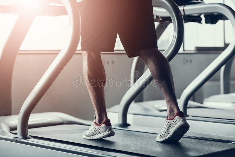 Fine in su Uomo in scarpe da tennis sulla pedana mobile in palestra fotografia stock libera da diritti