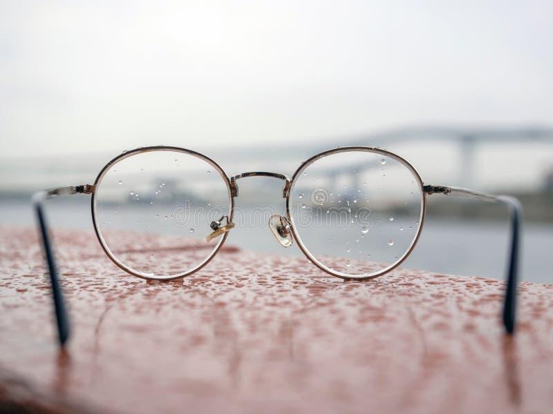 Fine sui retro occhiali tutta di stile coperta di gocce di acqua sulla lente fotografie stock