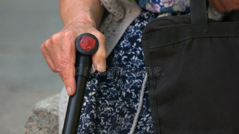 Fine sul bastone da passeggio della tenuta della mano della donna anziana fotografia stock libera da diritti