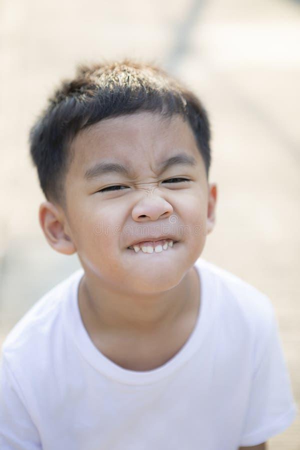 Fine sul dente e sul fronte scherzare dei bambini asiatici che stanno all'aperto fotografia stock