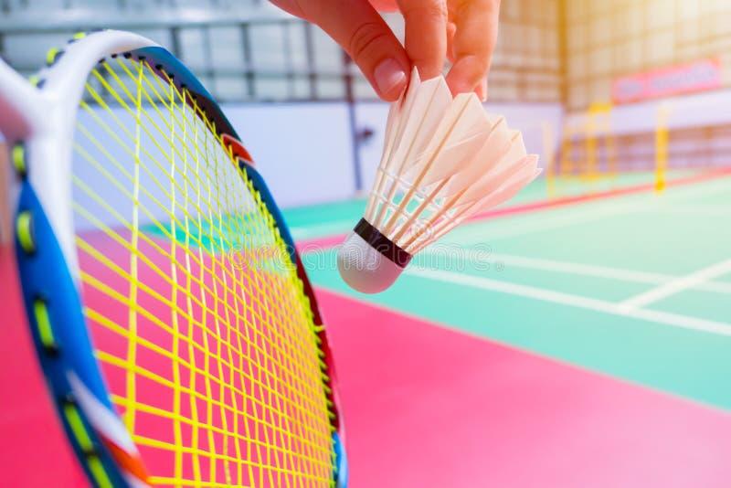 Fine sul fondo del campo da badminton di volano di volano di servire della tenuta della mano immagine stock