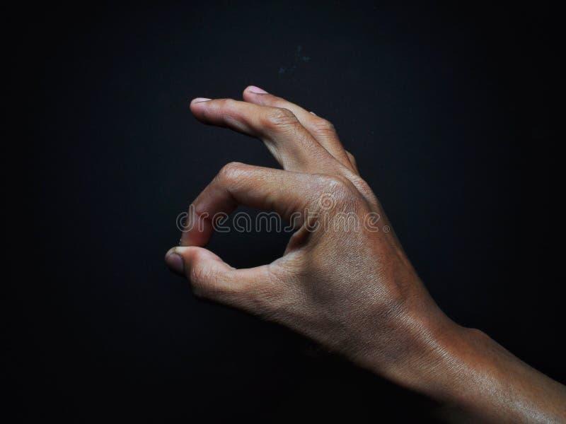 Fine sul gesto di mano di APPROVAZIONE isolato su fondo nero fotografia stock libera da diritti