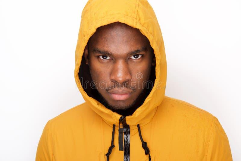 Fine sul giovane uomo di colore serio con il cappotto di pioggia contro fondo bianco fotografia stock libera da diritti