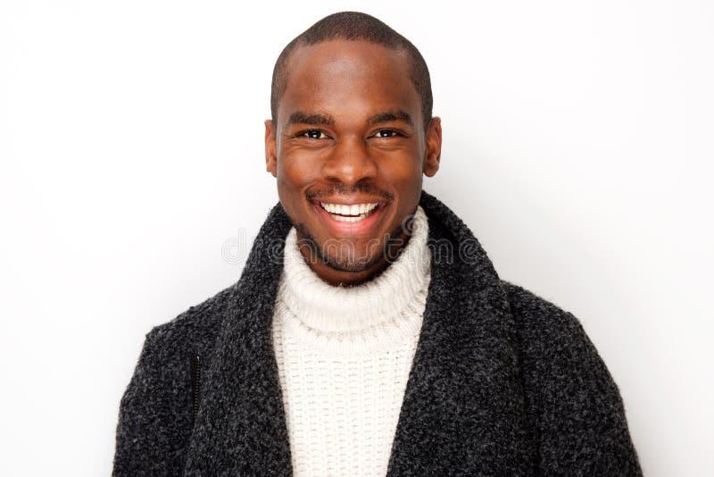 Fine sul giovane uomo di colore sorridente con il cappotto da fondo bianco isolato fotografia stock