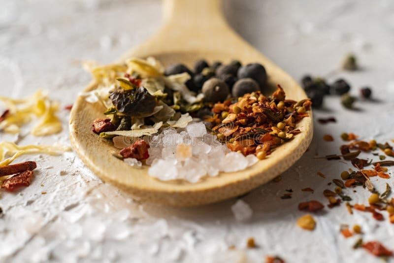 fine sul grande cucchiaio di legno con la miscela aromatica delle erbe dei peperoni e delle spezie, culinarys indiani immagini stock