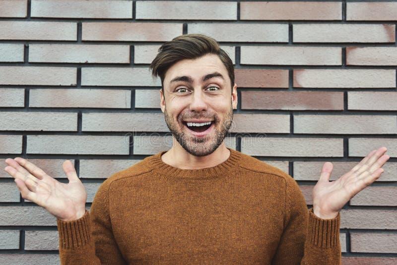 Fine sull'uomo bello felice di modo d'avanguardia che si appoggia vecchio muro di mattoni mentre esaminando la macchina fotografi immagini stock