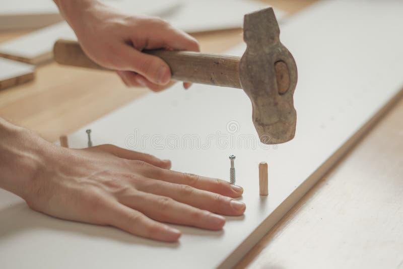 Fine sull'uomo che monta mobilia nuovissima con il martello sul pavimento di legno n fotografia stock