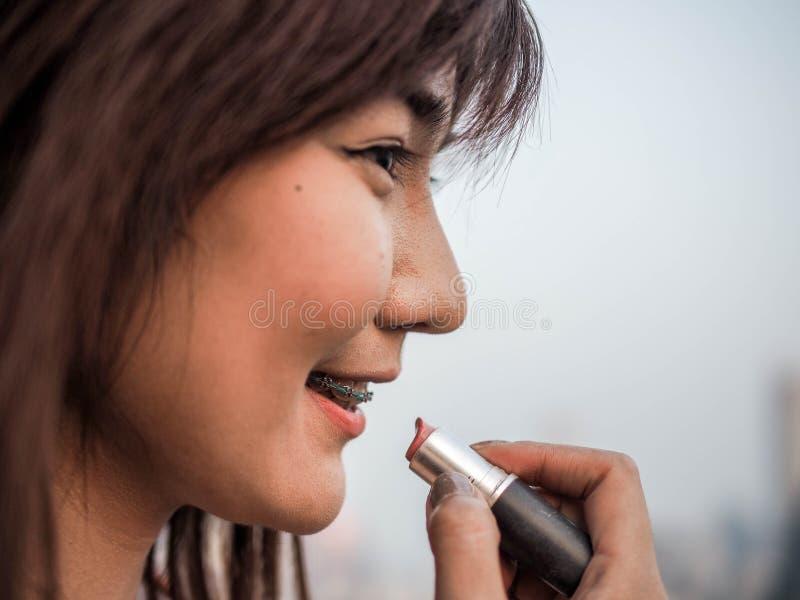 Fine sulla bella donna asiatica che mette il rossetto di trucco, concetto felice della donna, cinematografico immagine stock libera da diritti