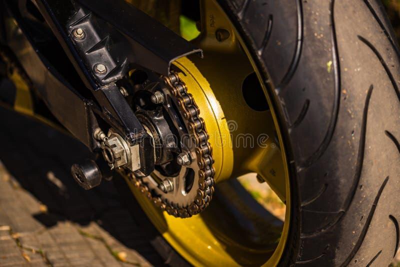 Fine sulla catena del motociclo e sulla ruota posteriore fotografia stock
