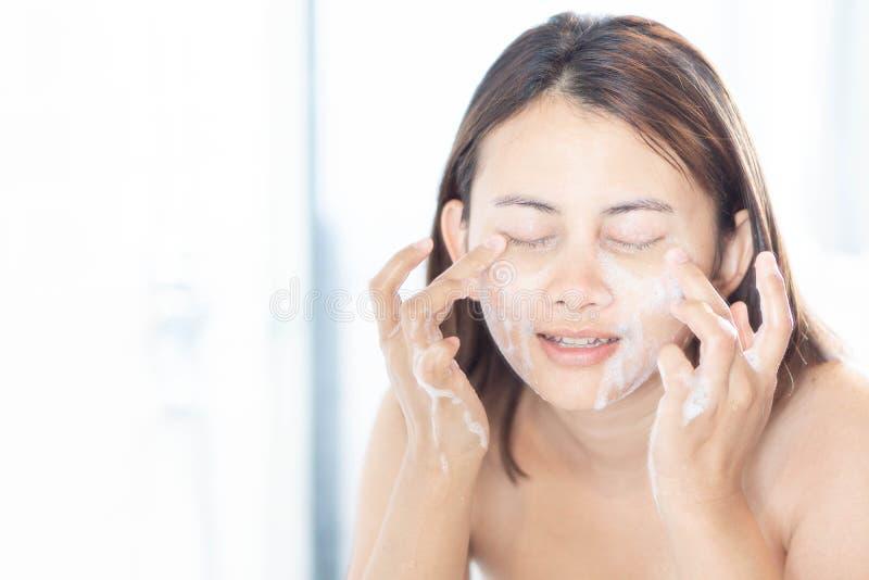 Fine sulla donna che guarda riflessione nello specchio per lavare fronte con schiuma nel concetto del bagno, di sanità e di belle immagine stock libera da diritti