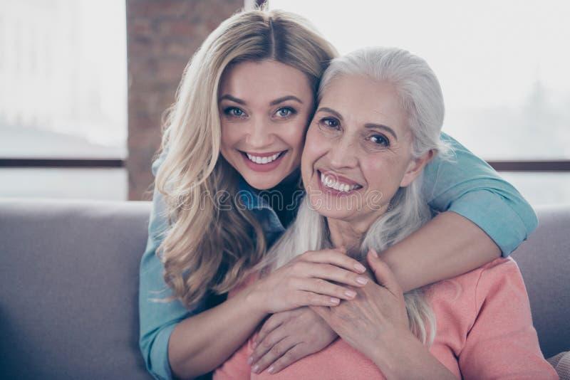 Fine sulla foto due che stupisce sua nonna della nonna del bambino della mamma delle signore che abbraccia il a due vie ha mancat immagine stock