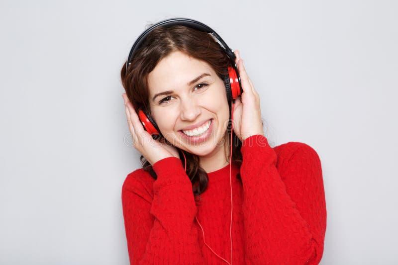 Fine sulla giovane donna che sorride con i telefoni capi dal fondo grigio immagine stock