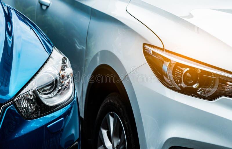 Fine sulla luce del faro dell'automobile blu e bianca di SUV Blu parcheggio accanto all'automobile bianca Concetto di industria a fotografie stock