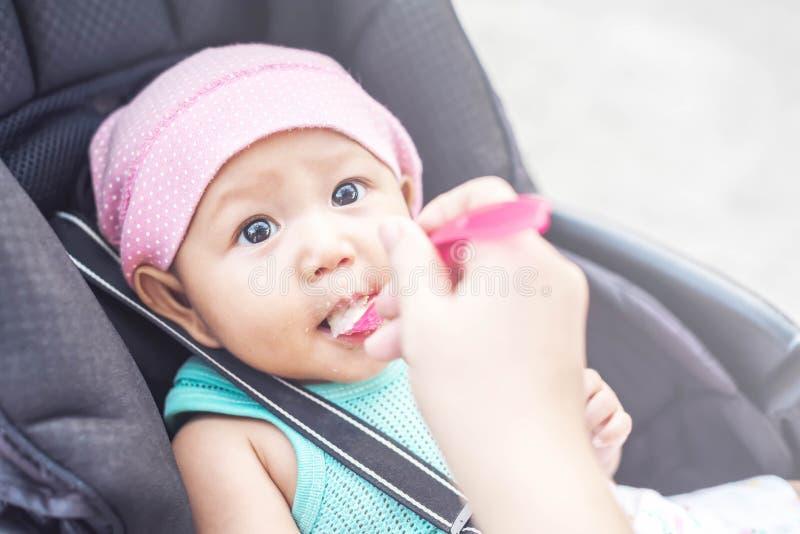Fine sulla mano della madre, un cucchiaio di alimenti per bambini che alimenta la sua piccola neonata sveglia per la cena Sguardo immagine stock
