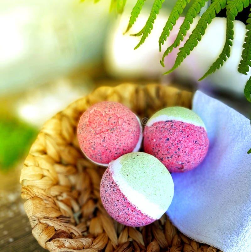 Fine sulla merce nel carrello rosa delle bombe del bagno con le foglie della felce su fondo di legno fotografia stock