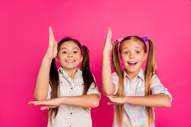 Fine sulla piccola piccola età della foto due le sue ragazze alza le armi a scuola che elemosina il tema di risposta dell'insegna immagini stock