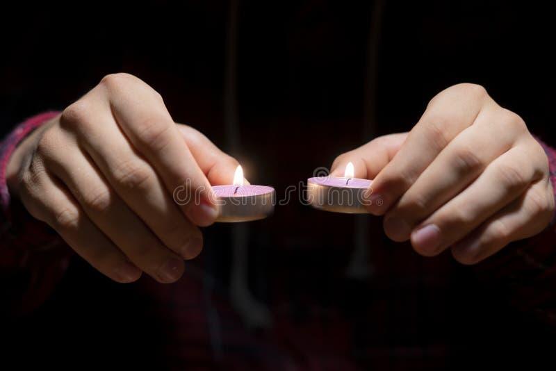 Fine sulle mani che tengono una candela nello scuro sopra la superficie di legno f fotografie stock